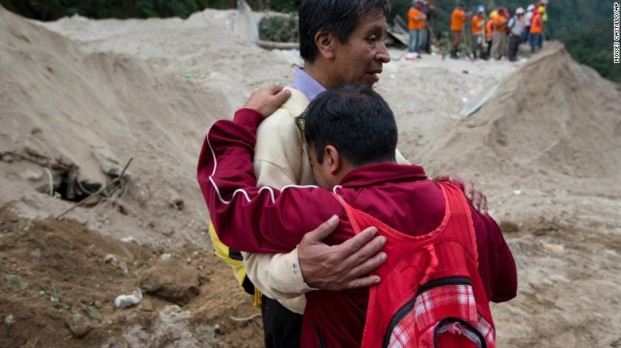 Neighbours comfort each other as rescuers continue the search for the townspeople. Photo: AP