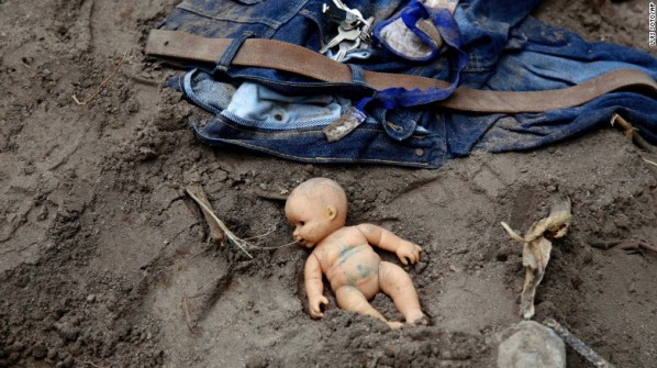 A doll and clothing lie in the mud as rescue workers continue to search the site Photo: AFP