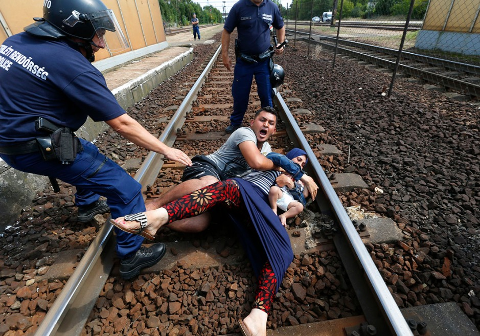 Hungarian policemen stand by the family of migrants as they wanted to run away at the railway station in the town of Bicske
