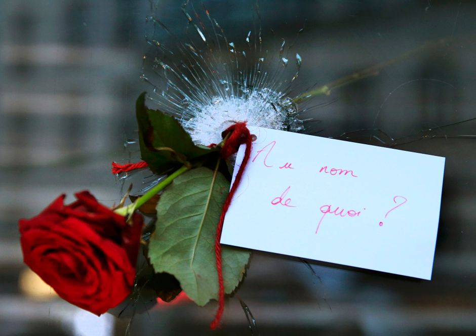 A rose placed in a bullet hole in a restaurant window the day after the attacks in Paris. The note reads