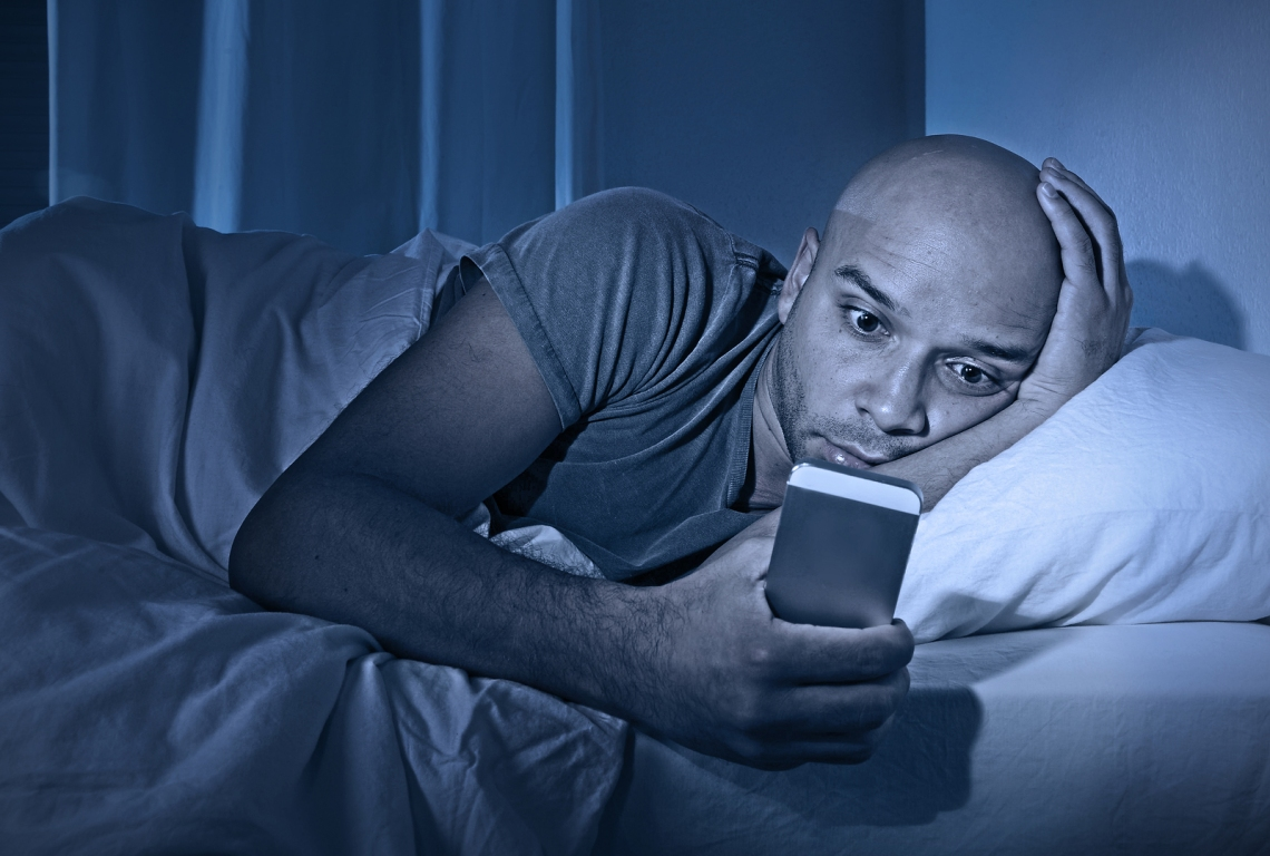 Young Cell Phone Addict Man Awake At Night In Bed Using Smartpho